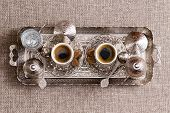 stock photo of pot roast  - Traditional ornate metal tray with two matching cups of freshly brewed Turkish coffee with sugar lids and a pot or cezve viewed from above - JPG