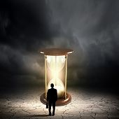 pic of hourglass figure  - Conceptual image with sandglass and rear view of businessman - JPG