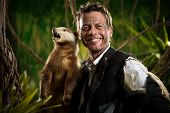 stock photo of badger  - Cheerful businessman in torn clothing smiling at camera and posing with a roaring badger in the jungle - JPG