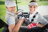 foto of buggy  - Golfing couple smiling at camera in their golf buggy on a sunny day at the golf course - JPG