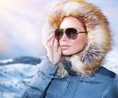 Luxury woman portrait in wintertime, wearing stylish sunglasses and warm coat with furry hood and looking away, winter fashion concept  poster