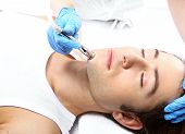 foto of beauty parlor  - Handsome man during microdermabrasion treatment in beauty salon - JPG