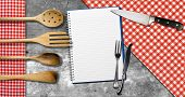 foto of knife  - Empty open notebook for recipes or menu with silver cutlery kitchen knife four kitchen utensils on grey wooden background with red and white checkered tablecloth - JPG