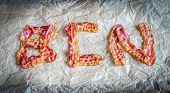 stock photo of bacon strips  - Fried Bacon Strips Put In Letters On The Baking Paper - JPG
