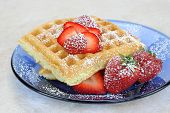 stock photo of confectioners  - Homemade waffles on a blue glass plate topped with fresh strawberries and confectioners sugar - JPG