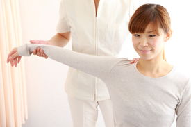 stock photo of chiropractic  - studio shot of young Japanese woman getting chiropractic - JPG