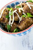 pic of cilantro  - Homemade Italian meatballs garnished with cilantro and parmesan cheese in a small bowl - JPG