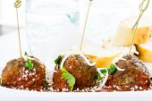 image of cilantro  - Large Italian meatballs garnished with cilantro and parmesan cheese as appetisers - JPG