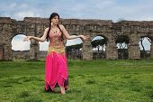 foto of aqueduct  - belly dancer with ancient Roman aqueducts ruins in the background - JPG