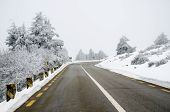 picture of icy road  - Asphalt mountain road with white snow on a winter scenery - JPG