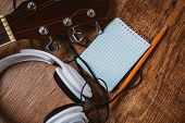 stock photo of risque  - headphone guitar notebook and pencil on wood - JPG