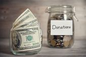 picture of coins  - Dollars and coins in glass jar with donations label - JPG