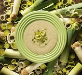 picture of leek  - Top view of a leek soup in a green bowl surrounded by fresh leek - JPG