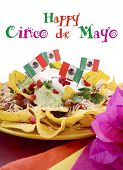 picture of nachos  - Happy Cinco de Mayo party table with nachos food platter and bright orange red and pink napkins on a red wood background - JPG