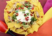 stock photo of nachos  - Happy Cinco de Mayo party table with nachos food platter and bright orange red and pink napkins on a red wood background - JPG