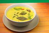 stock photo of curry chicken  - Hot and spicy chicken green curry on a green background on a wood table top - JPG