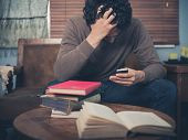 pic of upset  - A young man surrounded by books is sitting on a sofa and is looking upset as he is using his smartphone - JPG