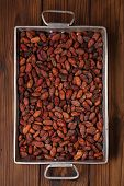 pic of cocoa beans  - roasted cocoa chocolate beans in Vintage heavy cast aluminum roasting pan on wood background - JPG