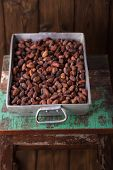 stock photo of cocoa beans  - roasted cocoa chocolate beans in Vintage heavy cast aluminum roasting pan on wood background - JPG