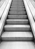 image of escalator  - Shining metal escalator moving up vertical monochrome photo with perspective effect - JPG