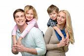 stock photo of piggyback ride  - Cheerful smiling family of four having fun - JPG