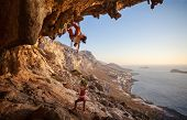 pic of cave woman  - Young woman lead climbing along a roof in cave with beautiful view in background - JPG
