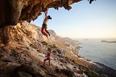 stock photo of cliffs  - Young woman lead climbing on overhanging cliff - JPG