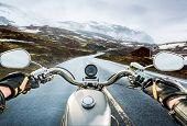 stock photo of slippery-roads  - Biker rides a motorcycle on a slippery road through a mountain pass in Norway - JPG