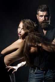 picture of moustache  - Young pair of sexual pretty girl with straight body with naked back and long hair standing near unshaven man with beard and moustache in waistcoat on black background copyspace vertical picture - JPG