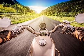 foto of biker  - Biker driving a motorcycle rides along the asphalt road - JPG