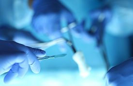 image of surgical instruments  - Surgeons hands holding surgical instrument while operating patient in surgical theatre - JPG