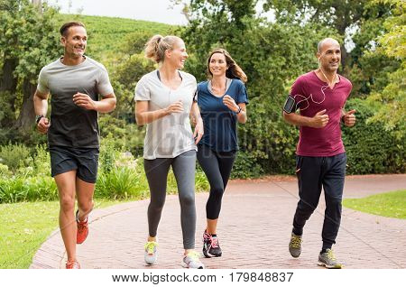 Healthy group of people jogging on track in park. Happy couple enjoying friend time at jogging park