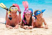 image of swimming pool family  - Three happy children laying on a tropical beach wearing snorkeling equipment - JPG