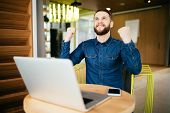 Happy Excited Young Businessman Sitting On Workplace And Celebrating Success poster