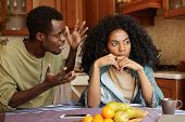 People And Relationships Concept. African American Couple Arguing In Kitchen: Man In Glasses Gesturi poster