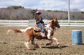 picture of barrel racing  - A young teenage girl turns around a barrel and races to the finish line - JPG