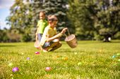 Kids Looking For Easter Eggs In The Park. Easter Eggs Hunt. Blurred Silhouettes Children With Basket poster