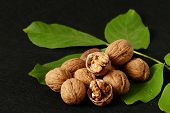 Dry Shelled Walnut And Green Walnut Leaves, On Black Background, Dry Shelled Walnut And Green Walnut poster