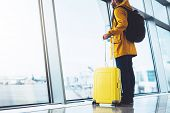 Tourist With Yellow Suitcase Backpack Is Standing At Airport On Background Large Window, Traveler Ma poster
