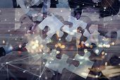 Business People Join Puzzle Pieces In Office. Concept Of Teamwork And Partnership. Double Exposure W poster