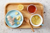 Lemon and ginger tea with honey. Wooden tray of honey lemon tea with fresh ginger root. poster