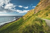 Steep green slope with tourist path. Northern Ireland. The grass covered hill next to the ocean. Ove poster