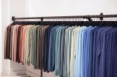 Clothes Hanger With T Shirt. Fashionable Clothing On Hangers In Shop. Sport Of T Shirts Are Hanging  poster