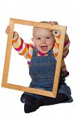 picture of vivacious  - Laughing vivacious little baby girl playing with an empty wooden picture frame looking through it at the camera - JPG