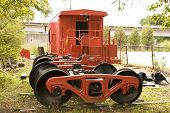 stock photo of caboose  - A red caboose and wheels by an old track - JPG