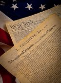 stock photo of preamble  - A copy of the constitution and the declaration of independence of the United States on a flag background - JPG