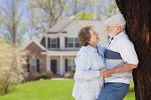 foto of yard sale  - Happy Senior Couple in the Front Yard of Their House - JPG