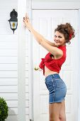 stock photo of girl next door  - Smiling woman holds pole next to white entrance door of house - JPG