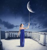 stock photo of reach the stars  - Young girl takes the Moon with rope - JPG