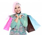 pic of fitri  - Woman in head scraf holding a few shopping bags and looking at camera - JPG
